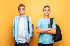 Portrait of two happy stylish guys, teenagers, isolated on yellow background stock images