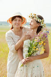 Portrait of two happy women. With flowers in summer field stock image