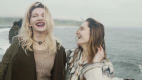 Portrait of two happy women standing on the black beach in Iceland and having fun together, jumping and smiling. Traveling female enjoying the beautiful stock footage