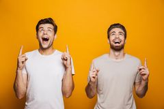 Portrait of a two happy young men best friends pointing. Fingers up at copy space over yellow background royalty free stock photos
