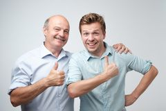 Portrait of a two happy young men showing thumbs up over gray background. Mature son and father are pleased with good family event royalty free stock image