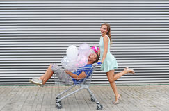 Portrait of two happy young people dating and having fun. Boy sitting in shopping cart and keeping color balloons in hand. Girl rolling trolley. Striped Stock Photos