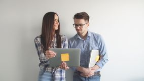 Happy mix-race couple holding laptop computer while standing and celebrating isolated over gray wall background. Portrait of two heterosexual colleagues in stock video