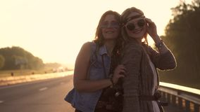 Portrait of two hippie girls. girlfriend in sunglasses in clothing a Boho style. Girls hippie dancing at dawn. two young girls carelessly having fun stock video footage