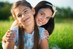Portrait of two hispanic teen girls. Portrait of two hispanic teens girls resting on meadow Royalty Free Stock Photo