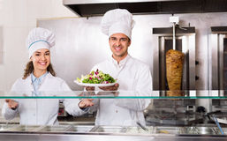 Portrait of two hospitable chefs with kebab Royalty Free Stock Photos