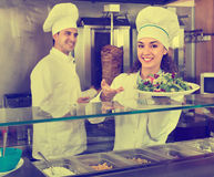 Portrait of two hospitable chefs with kebab at fastfood place Stock Images