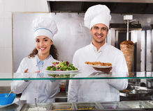 Portrait of two hospitable chefs with kebab at fastfood place Royalty Free Stock Image