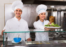 Portrait of two hospitable chefs with kebab at fastfood place Stock Photos