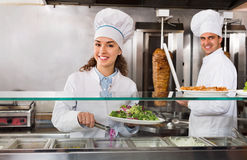 Portrait of two  hospitable chefs with kebab at fastfood place Royalty Free Stock Photos