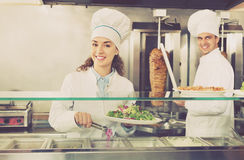Portrait of two  hospitable chefs with kebab at fastfood place Stock Photo