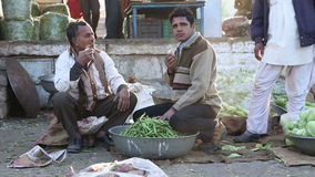 Portrait of two Indian man sitting on ground at market and drinking hot chai. stock footage