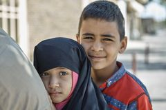Portrait of two Iranian children on city street, Yazd. Iran. Yazd, Iran - April 21, 2017: Close-up portrait, two Iranian children, boy and girl of primary Stock Image