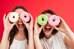 Portrait of two joyful happy girls. Posing while holding donuts at their faces isolated over red background Royalty Free Stock Photo