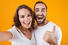 Portrait of two joyful people man and woman smiling while taking selfie photo, isolated over yellow background stock photography