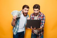 Portrait of a two joyful young men using laptop. Computer while holding money banknotes and celebrating isolated over yellow background Stock Photography