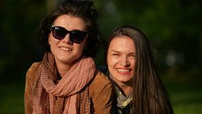 Portrait of Two Joyous Girls Looking at the Camera and Smiling Together Having Fun in the Park. Attractive Brunettes. Enjoying Sunny Spring Day Outdoors, HD stock video