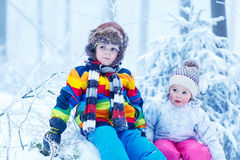 Portrait of two kids: boy and girl in winter hat in snow forest. At snowflakes background. outdoors winter leisure and lifestyle with children on cold days Royalty Free Stock Images