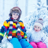 Portrait of two kids: boy and girl in winter hat in snow forest Stock Photos