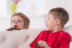 Portrait of two kids eating in white sofa. Stock Photo