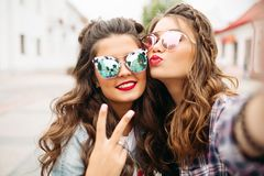 Gorgeous brunette girlfriends with hairstyle, mirrored sunglasses and red lips making selfie with duck face. Portrait of two ladies with red lips and wavy hair royalty free stock image