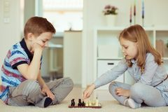 Portrait of two little children concentrated playing chess Stock Image