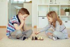 Portrait of two little children concentrated playing chess Stock Photography