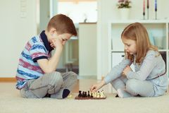 Portrait of two little children concentrated playing chess Stock Photos