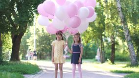 Portrait of two little girls with balloons in their hands. happy carefree children in the summer Park. Children run through the Park with a huge bunch of stock video