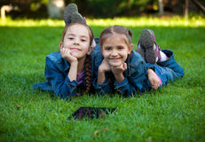 Portrait of two little girls lying on grass with tablet Stock Photography