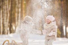 Portrait of two little girls play with snow in a park in winter Stock Images