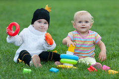Portrait of two little girls playing on the grass Stock Images