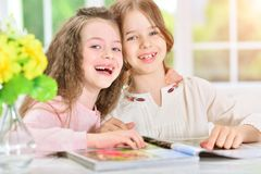 Girls reading magazine. Portrait of two little girls reading magazine royalty free stock photography