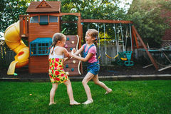 Two girls splashing each other with gardening house on backyard on summer day royalty free stock image