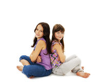Portrait of a two little girls sitting back to back and smiling. On white background stock photography
