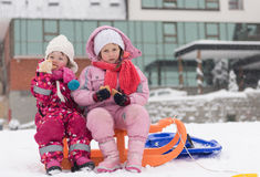 Portrait of two little grils sitting together on sledges Stock Photos