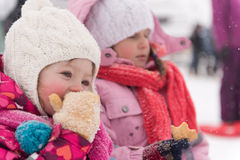 Portrait of two little grils sitting together on sledges Stock Images