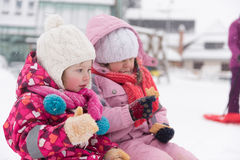 Portrait of two little grils sitting together on sledges Royalty Free Stock Photography