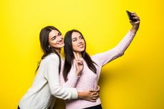Portrait of two lovely girls dressed in sweaters standing and taking a selfie. Over yellow stock image