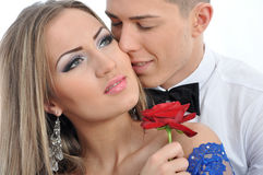 Portrait of two lovers embrace, she is holding a rose. Portrait of two lovers embrace, she is holding  a rose isolated on white background Royalty Free Stock Photo
