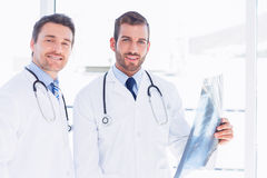 Portrait of two male doctors examining xray Stock Images