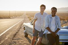 Portrait Of Two Male Friends Enjoying Road Trip Standing Next To Classic Car On Desert Highway stock photo