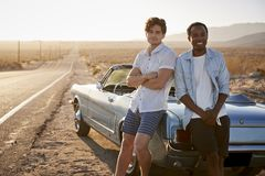 Portrait Of Two Male Friends Enjoying Road Trip Standing Next To Classic Car On Desert Highway stock image