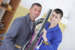 Portrait two male mechanics either side bicycle. Portrait of two male mechanics either side of a bicycle Stock Photo