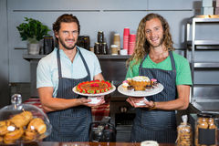 Portrait of two male staffs holding dessert on cake stand at counter Royalty Free Stock Photography