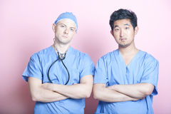 Portrait of two male surgeons standing with arms crossed over pink background Stock Photo