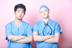 Portrait of two male surgeons standing with arms crossed over pink background Royalty Free Stock Photos