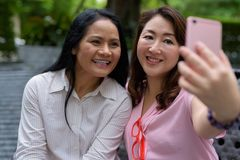 Two mature Asian women together outside the mall in Bangkok city. Portrait of two mature Asian women together outside the mall in Bangkok city Stock Photo