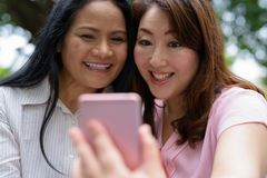 Two mature Asian women together outside the mall in Bangkok city. Portrait of two mature Asian women together outside the mall in Bangkok city Stock Photos