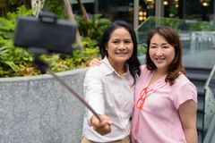 Two mature Asian women together outside the mall in Bangkok city. Portrait of two mature Asian women together outside the mall in Bangkok city Stock Image